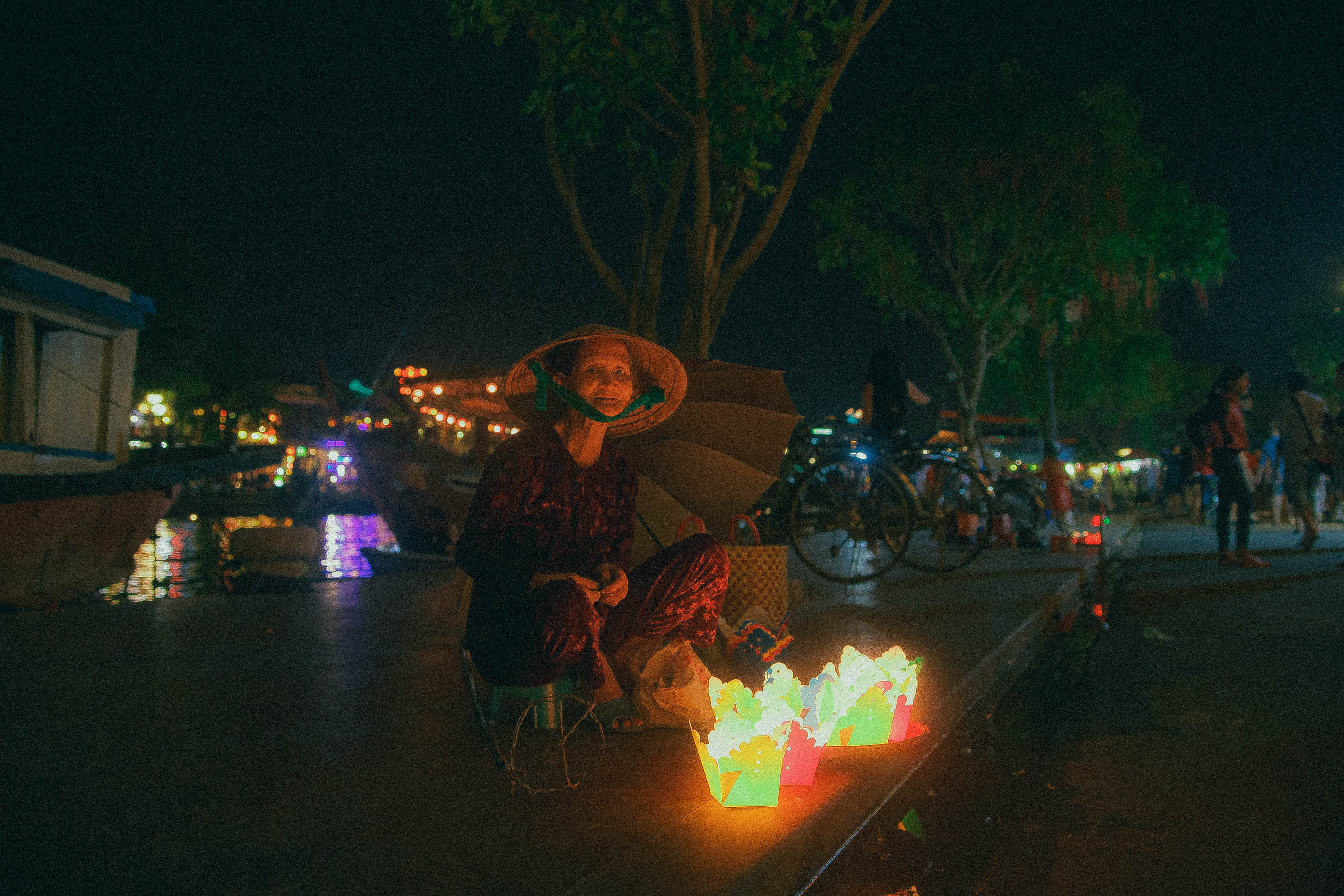 local vietnamese lady lightning a candle in ancient lantlern city hoi an south east asia ambient market river side